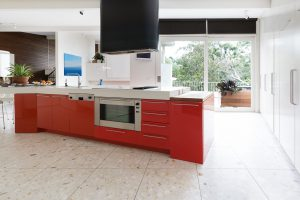 Orange red kitchen cabinets in island bench in modern luxury Aus